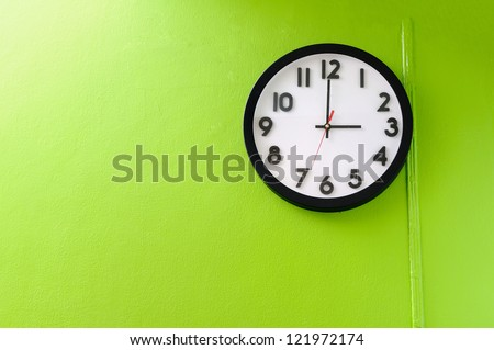 Clock showing 3 o'clock pm on a green wall