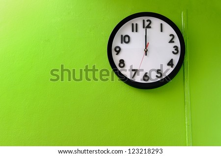 Clock showing 12 o'clock pm on a green wall