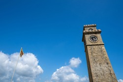 Clock tower of Galle Fort with the Sri Lanka flag blowing in the wind. Negative space composition with extra copy space