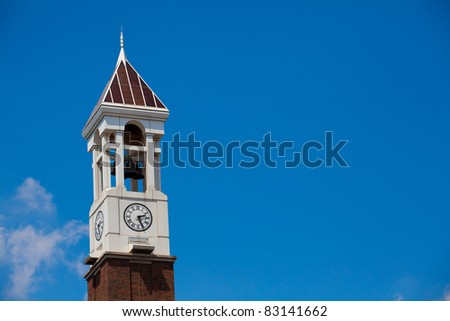 Clock tower with bells on clear blue sky