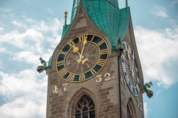 Clock wall on the tower of the ancient building in the city center of Zurich, Switzerland. Fraumunster church