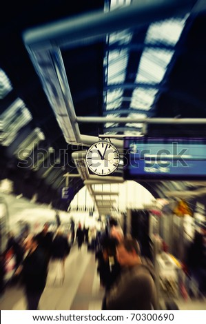 Clock watch in modern train station (Grand Central Station). Frankfurt am Main, Germany. Selected focus on clock. Peoples are blurred to show dynamic movements
