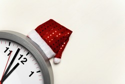 Clock with a Christmas cap on a white background.