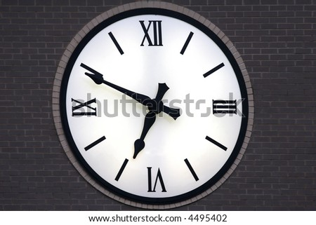 Clock with backlighting at dusk showing eleven minutes before seven