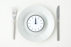 Clock with 12 o'clock on white plate with fork and knife