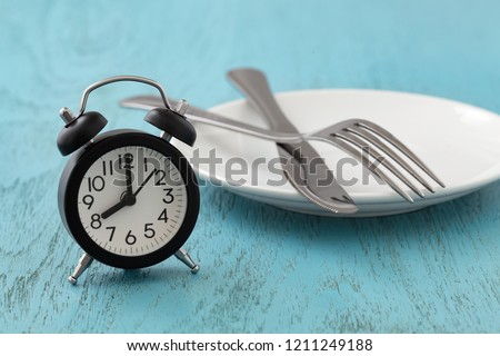 Clock with white plate, fork and knife, intermittent fasting, diet, weight loss concept on blue wooden table #1211249188