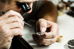 Clockmaker repairing wrist watch. Macro shot.