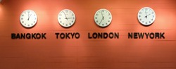 Clocks on a Orange awall, Four wall clocks showing time in different capitals of the world, selective focus, soft focus