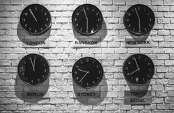 Clocks shows different time zones. Business office concept. Loft interior wallpaper. Vintage effect.