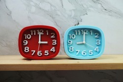 Clocks with time zone of different country on wooden shelves and marble background