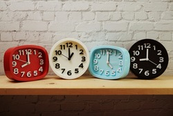 Clocks with time zone of different country on wooden shelves and white brick wall background