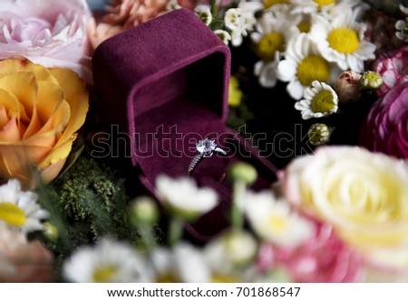 Cloeseup of Wedding Ring in Red Box with Flowers Arrangement Decoration