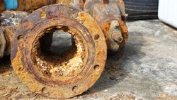 Clogged metal pipes. Suspended solids in water contaminated with iron and manganese can cause scale and rust to clog up in water pipes. On the background of a cement floor with a copy area. selective
