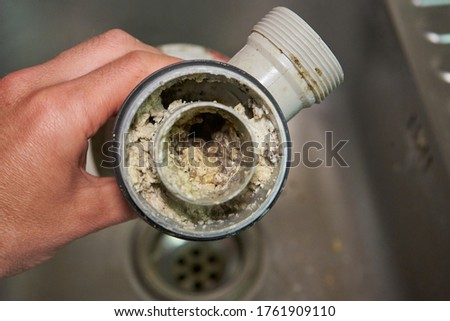 clogged sink pipe,in the hands of a clogged dirty sewer pipe from leftover food Stockfoto ©