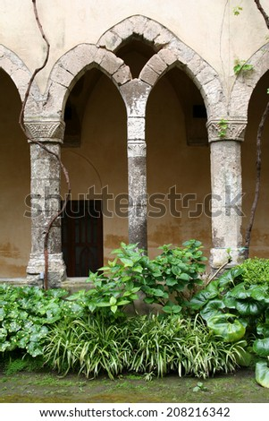 Cloister architecture. Gothic arch and shrubbery.
