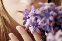 close a part of a girl smelling flowers