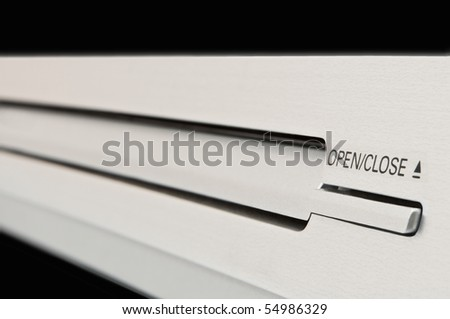 Close and low level angle capturing a portion of a silver dvd player with disc tray and operating buttons in focus. Arranged over black.