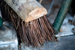Close and selective focus of the bristles of a wooden broom in a garden shed with intentional shallow depth of field and bokeh