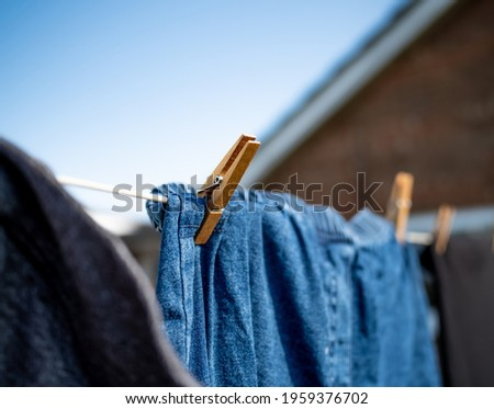Close and selective focus on a wooden clothes peg keeping a pair of blue denim pants or jeans on a washing line with intentional shallow depth of fiels and bokeh Foto stock ©
