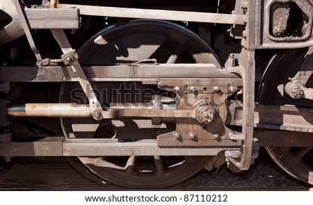 Close detail image of the drive wheel of an old steam locomotive engine