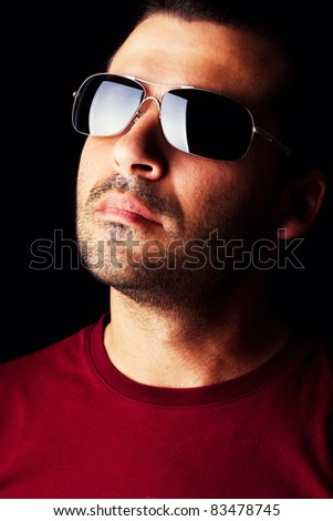Close detail view of a young male man with dark shades  isolated on a black background.
