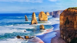 Close encounter of limestone rocks dubbed apostles in twelve apostles marine park on Great Ocean road in Victoria, Australia. Bright sunny day and calm blue ocean.