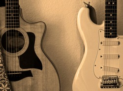 Close frame in sepia tone of part of body of an acoustic guitar showing sound hole, bridge and part of neck next to part of the body of a white electric guitar showing pickups, bridge and part of neck