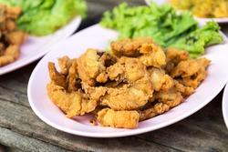 Close-fried crispy fish pieces on a plate heaped with old wooden floors appetizing.