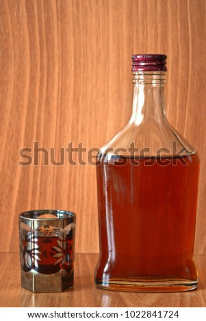 close glass bottle and pattern cup of brown strong whiskey on wooden table