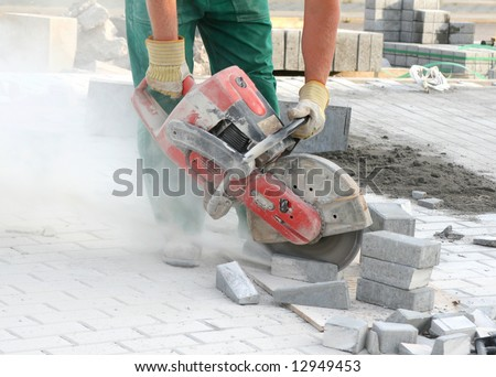 Close look at the worker with concrete saw in his hands and working, dusty workplace