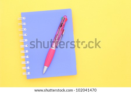 Close note book and ballpoint pen