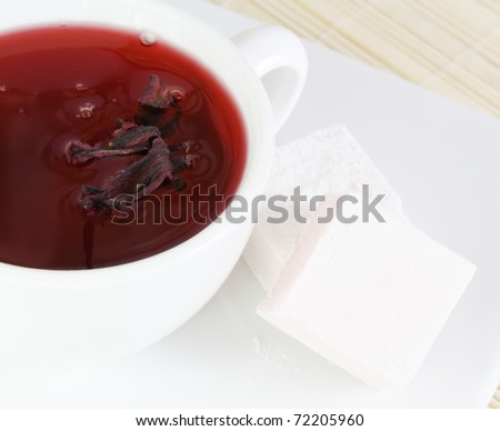 Close of a Cup of Red Tea and Sweets