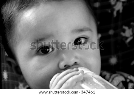 Close of a little baby boy drinking a bottle