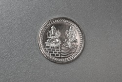 Close of a silver coin engraved with images of Goddess Lakshmi and Lord Ganesha.