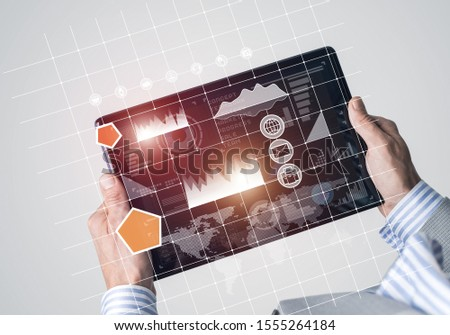 Close of businessman hands holding tablet pc with infographs on screen #1555264184