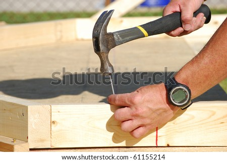 close of hands with hammer