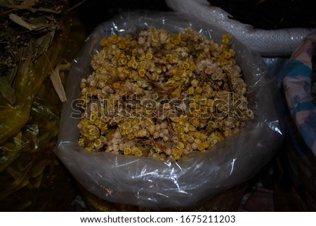 Close-op of Dried immortelle herb in a transparent bag n a local street market in the village. Dried herbs and spices shop. Herbs for medical treatment. Exploring villages of Azerbaijan Foto stock ©