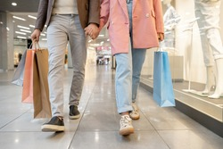Close-p of young couple holding hands and walking together in shopping mall with purchases