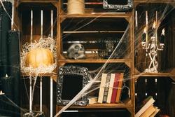 Close photo. Decor for Halloween on the shelves of the closet. Skull, pumpkins, cobwebs, books, candlesticks on shelves decorated for Halloween. Background