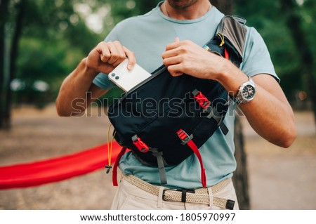 Close photo of a waist bag for advertising. A man in casual clothes puts a white smartphone in the pocket of his waist bag. Stock foto ©