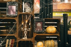 Close photo of Halloween scenery with cobwebs in the web, candles, pumpkins, old photo frames and books. Background.