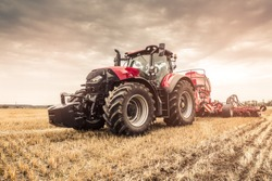 Close photo of modern red tractor with red implement seeding directly into the stubble using GPS for precision farming after a harvest with combine before the Winter.