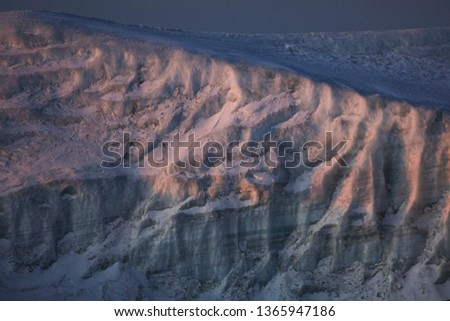 Close picture of an iceberg, texture of an ice layers and snow cover. Landscape of the wild nature in winter, cold region. Sun rays laying on the surface. #1365947186