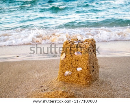 Close picture of sand castle remains with seashells, sea waves in the background, Bulgarian Black Sea Coast at Primorsko
