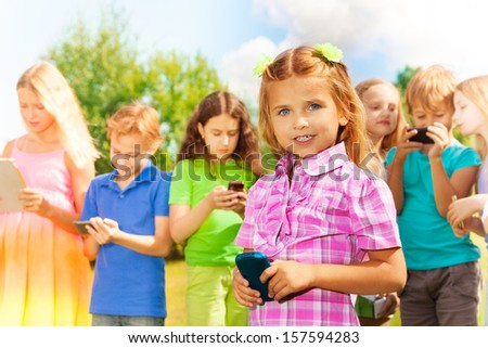 Close portrait Little girl with standing and texting with the phone standing in the park with group of friends #157594283