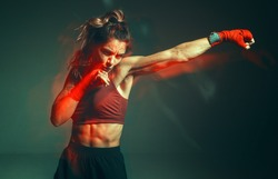Close portrait of a female mixed martial arts fighter with a bandage on her hands. Long exposure shot