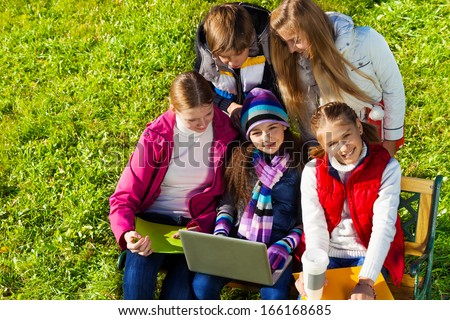 Close portrait of a group of five school kids, boy and girls sitting on the bench in autumn park with laptop at sunny day, happy and smiling