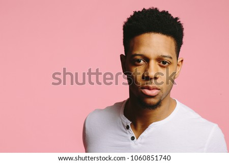 Close portrait of a serious young African American man in white shirt on pink background