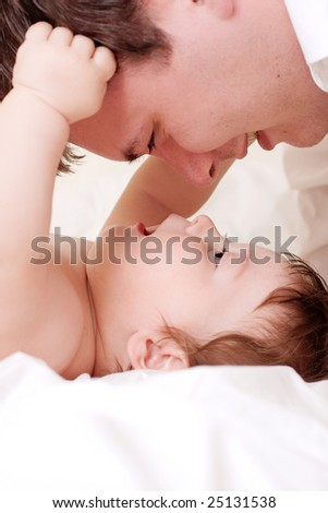 close portrait of beautiful baby play with father