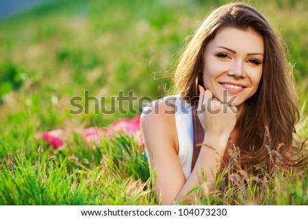 Close portrait of beautiful young woman on green grass in the summer outdoors